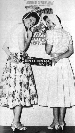 Two women holding a centennial sign